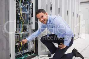 Technician plugging cable into server