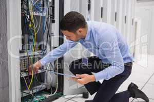 Man checking tablet pc as he is plugging cables into server