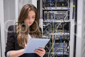 Woman using tablet pc in front of servers