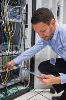 Man using tablet pc to work on servers