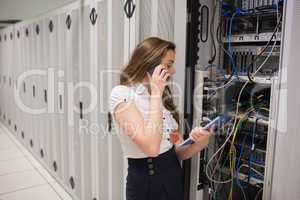 Woman on the phone holding tablet pc checking the servers