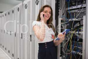 Smiling woman on the phone holding tablet pc and checking server