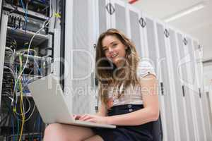 Smiling woman with laptop working with servers