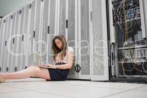 Woman sitting on floor working on laptop