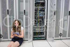 Smiling woman sitting on floor checking servers with tablet pc