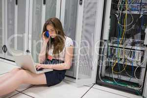 Woman checking the servers with laptop and talking on phone