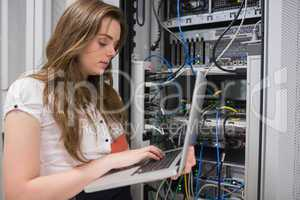 Woman using laptop to work on servers