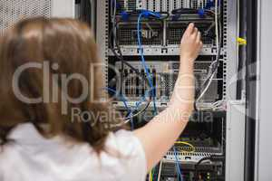 Woman fixing wires of servers