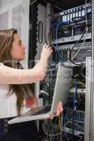 Woman adjusting server wires and holding laptop