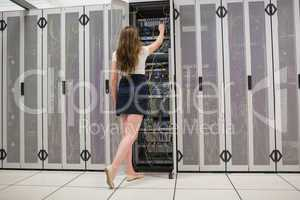 Woman standing in the hallway and fixing wires in data center