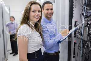 Two smiling  technicians checking the servers