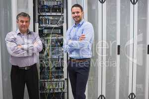 Two smiling men standing in front of servers