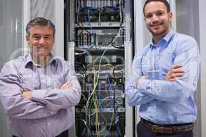 Technicians smiling while standing in front of servers