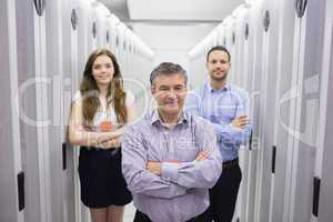 Three smiling people standing in data center