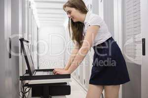 Woman doing maintenance on servers with a laptop