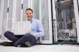Smiling man sitting on floor checking servers with laptop