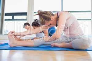 Women in head to knee forward bend pose in yoga class