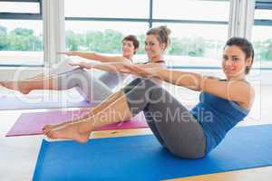 Happy women in yoga class doing boat pose