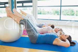Women doing sit ups with exercise ball