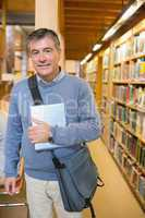Man standing next to shelves in a library
