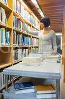 Librarian looking through book shelf