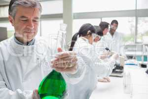 Chemist viewing liquid while other persons doing research