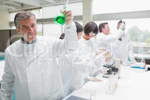 Chemist raising beaker of green liquid