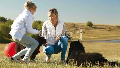 Mother and Daughter Feeding their Newfoundland Dogs