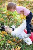 beautiful young mother and her daughter lying on the autumn leav