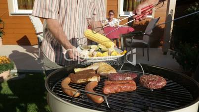 seniors putting meat and vegetables on kettle barbecue