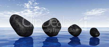 Black stones on blue water
