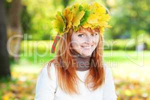 portrait of a beautiful young redhead teenager woman in a wreath