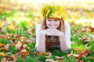 young redhead teenager woman in a wreath of maple leaves lying o