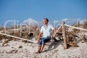 junger mann entspannt am strand in dünen