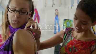 Fashion designer using measuring tape with female client in studio