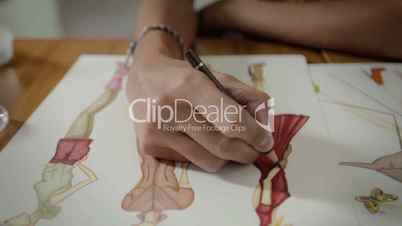 Team of young female fashion designers drawing dress in studio