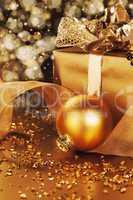 goldene christbaumkugel neben weihnachtsgeschenk