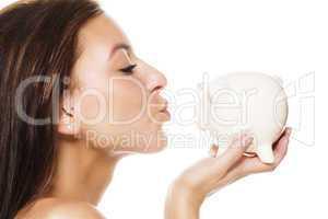 schöne junge frau küsst sparschwein