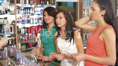 Sales Person Assisting Female Shoppers in Choice of Cosmetics
