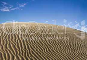Wellige Dünen mit blauem Himmel