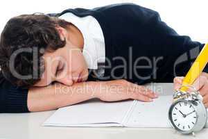 Teenager dozing off while writing his test