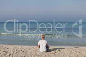 Mann macht yoga Sport am Strand Querformat