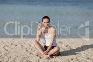Frau trinkt wasser aus einer flasche am Strand Querformat