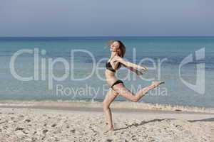 Frau mit Bikini springt fröhlich am Strand Querformat
