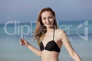 Junge Frau mit Bikini lachend am Strand Portrait Querformat