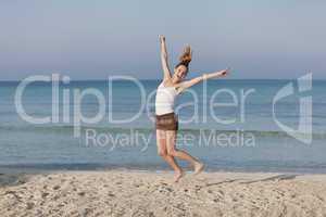 Fröhliche Frau springt lachend am Starnd Querformat