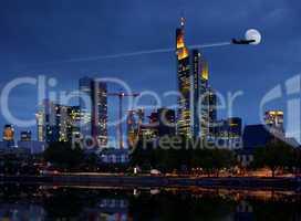 Skyline Frankfurt am Main zur blauen Stunde am Abend mit Flugzeug