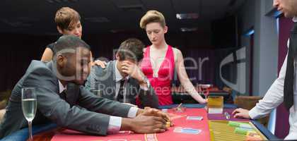 Women comforting man as other man takes jackpot