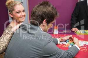 Woman smiling as man is taking winnings