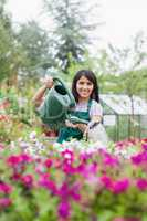 Cheerful woman working in garden center watering the plants